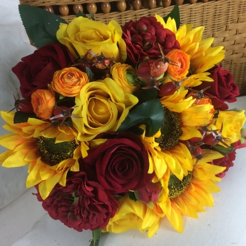 a brides bouquet of artificial silk Sunflowers, roses berries and ranunculas