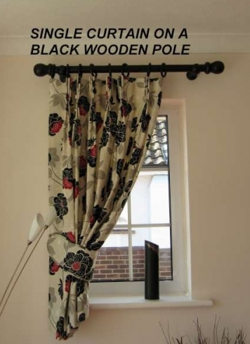Made to measure wooden curtain pole in a small window with single curtain and piped tie back in Ferring, West SussexSingle Curtain On A Black Wooden Pole