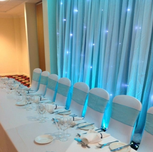 Fairy light Backdrop With Uplighters White Chair Covers Linen Napkins Organza Sashes