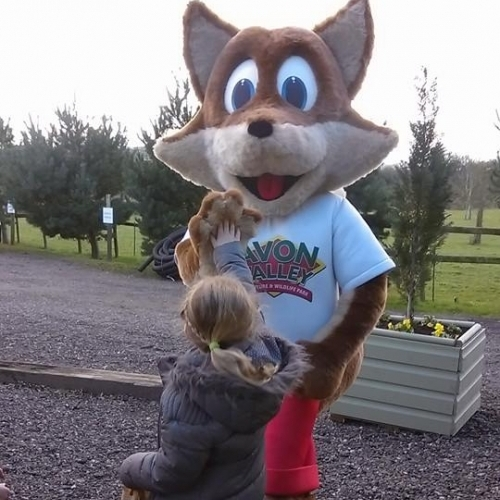 Felix the Fox high-fives young visitor